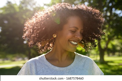 Laughing young woman standing outside in a park on a sunny summer afternoon twirling her curly hair