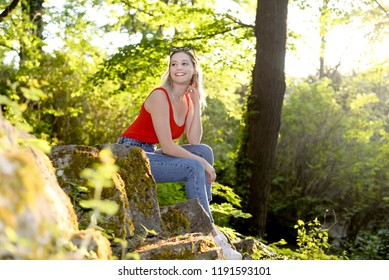 laughing young woman with sunglasses sitting in the park