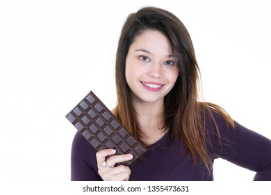 Laughing young woman in sweater holding in hand chocolate bar isolated on white wall background