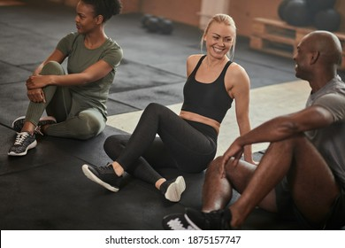 Laughing young woman talking with a group of diverse young friends while sitting on a gym floor after a workout