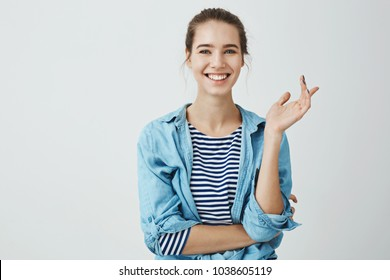 Laughter eases everyday problems. Charming woman in trendy outfit with bun hairstyle gesturing while talking to friend, standing with crossed hand over body and smiling broadly at camera