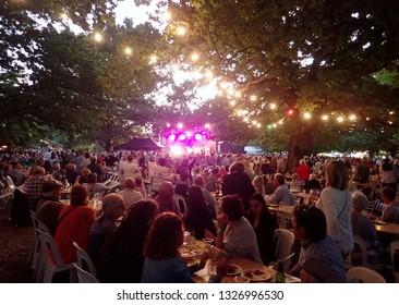 Launceston, Tasmania, Australia - 2 February 2019: Dusk settles on the Launceston Festivale with large groups of people enjoying the food and music in the City Park grounds.
