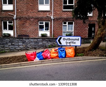 Launceston, UK, July, 17 2012. Colorful rubbish trash refuse bags lined up on pavement for collection. Funny outbound traffic sign juxtaposition. Concept removal journey, recycling, travel direction