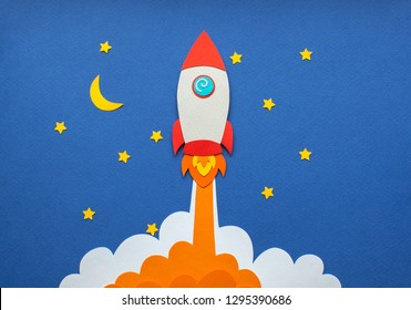 The launch into space. Flying rocket through the clouds. Start up of the space rocket. Rocket ship in flat design on blue background. 3d paper r. Concept of business launch. Paper cut.