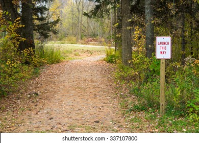 """Launch This Way"" sign next to winding path leading into trees.  Soft focus on background to allow for copy.  Applicable concepts could include Product Launch, Beginnings, Exploration, or others."