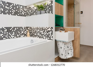 Laundry bag in wooden cabinet of modern bathroom
