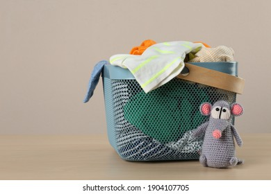 Laundry basket with different children's clothes and toy on wooden table. Space for text