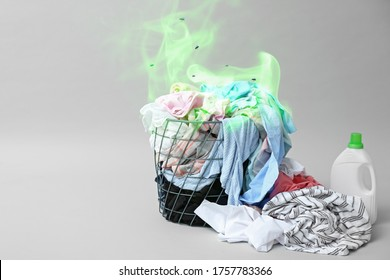 Laundry basket with dirty clothes on grey background