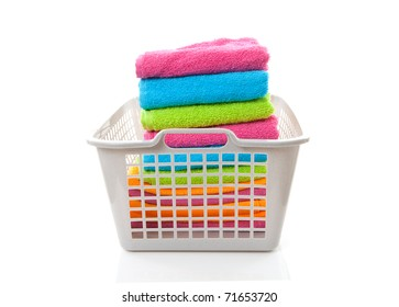 Laundry basket filled with colorful folded towels over white background