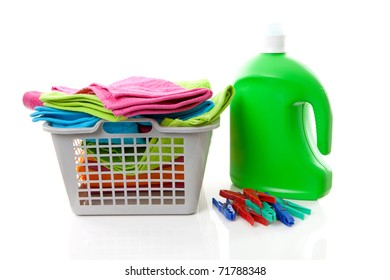 Laundry basket filled with colorful folded towels, pegs and bottle over white background