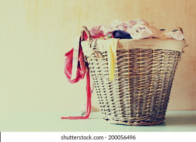 laundry basket full with clothes. vintage toned image.
