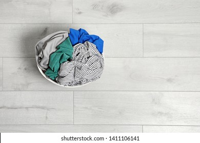 Laundry basket full of dirty clothes on floor, top view. Space for text