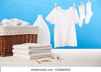 laundry basket, plastic container with laundry liquid, pile of clean soft towels and white clothes hanging on clothesline on blue