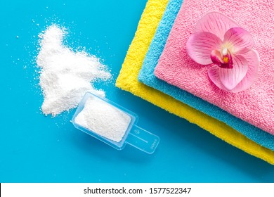 Laundry concept. Clean linen and orchid near washing powder on blue background top view