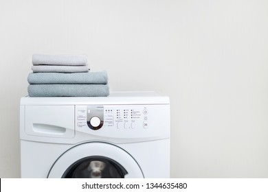 Laundry concept. Cropped photo of white and modern washing machine with fresh towel on top standing isolated inside bright apartment light interior