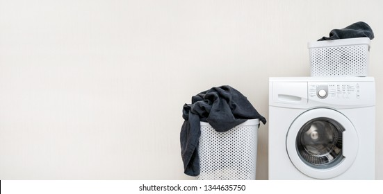 Laundry concept idea. White washing machine with two basket of black linen standing isolated inside apartment with light interior and copy space for text