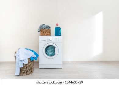 Laundry concept. White washing machine with gel soap and basket of clothes standing against wall inside bright and beautiful apartment interior