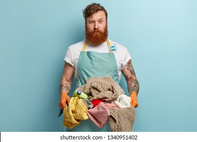 Laundry day concept. Serious bearded red haired Caucasian man busy doing housework, holds basket full of dirty clothes, wears apron with clothespins, protective gloves uses washing detergent