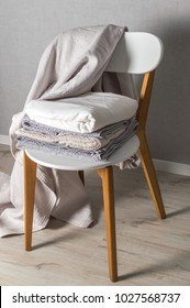 Laundry day. Stack of home linen on the chair in scandinavian style.