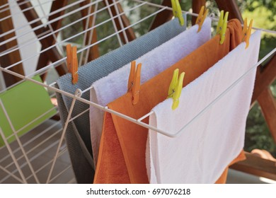 Laundry drying , clean colorful towels on a clothes horse outside.