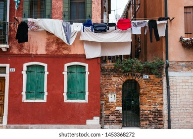 laundry drying on a rope near the open window on the streets of Venice, Italy