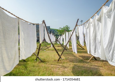 Laundry drying on a rope in the yard in the sunlight. White bed sheets and towels drying in indian traditional laundry Dhobi Ghat in Fort Kochi