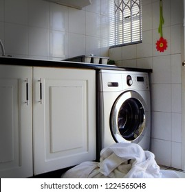 Laundry in front of washing machine in all white kitchen