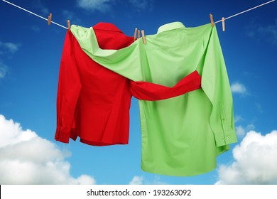 Laundry hanging on a clothesline concept for love and romance with two shirts embracing each other looking at a blue sky