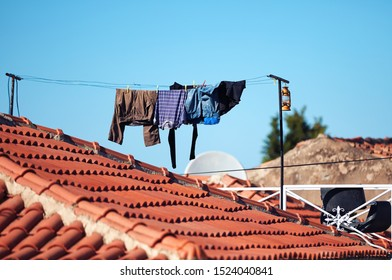 Laundry hanging on the roof of a building, clothes in laundry line drying on the roof of a house