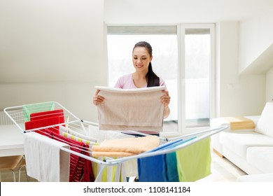laundry and household concept - happy woman or housewife taking bath towels from drying rack at home