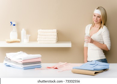 Laundry ironing - woman break with drink after housework
