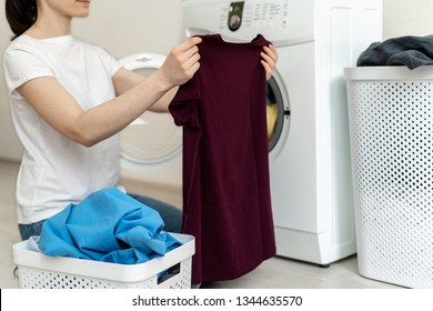 Laundry process. Profile side view photo of attractive and beautiful woman holding fresh t-shirt in her hands against washing machine inside bright light flat interior