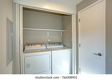 Laundry room hidden behind white folding closet doors with white washer and dryer.