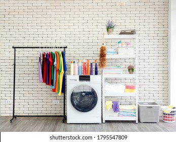 Laundry room interior. Utility room with washing machine, cleaning equipment, various home cleaner, clean wipes and colorful clothes hanging on the clothesline on white vintage brick wall background.