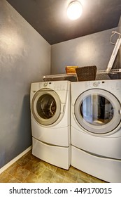 Laundry room with tile floor, blue walls, washer, and dryer.