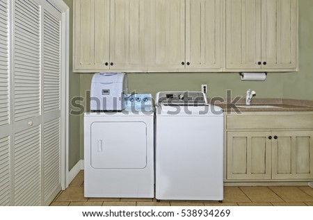 A laundry room with washer,dryer,ice maker,sink,cabinets,and a pantry area.  The cabinets have a light antiqued finish on them.