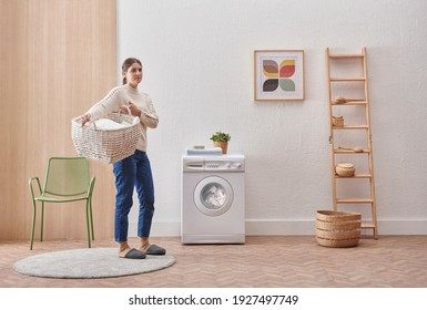 Laundry room washing machine and dirty clothes decorative modern style. Woman is keeping clothes basket.