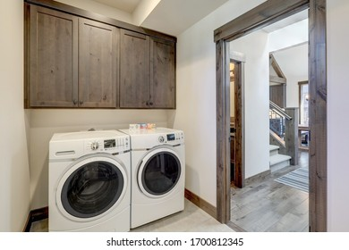 Lavandería con lavavajillas y secadora blancas y armarios de madera marrón oscura.