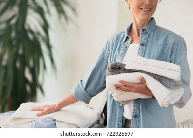 Laundry service concept, close up photo of woman holding a pile of ironed clean towels standing at ironing board and smiling