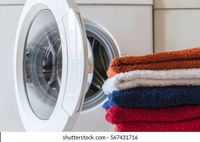 Laundry service, housework, washing machine and a stack of colorful towels./Washing machine and towels