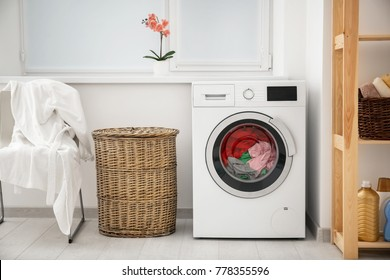 Laundry in washing machine and basket indoors - Shutterstock ID 778355596