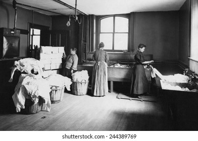 Laundry with women working at large sinks, one operating a hand cranked wringer, and another at a drying rack placed near a stove. Boston, Massachusetts, 1905.