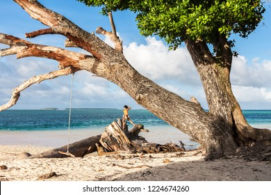 Laura beach. Azure blue turquoise waters of lagoon. Majuro atoll, Marshall islands, Micronesia, Oceania.  Woman tourist makes a photo standing on a stump. Bungee, rope swing, branches of a dead tree