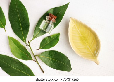 Laurel bay oil in bottle and ceramic plate with fresh green aroma leaves, top view white wooden table