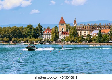 Lausanne, Switzerland - August 26, 2016: Motorboat and man wakeboarding at Lake Geneva embankment near Chateau Ouchy in Lausanne, Switzerland.