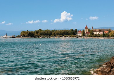 Lausanne, Switzerland - August 26, 2018: Chateau Ouchy at Lake Geneva promenade of Lausanne, Switzerland. People on the background