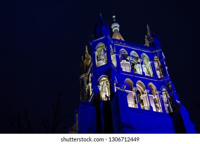 Lausanne, Switzerland - DECEMBER 2018: Night illuminated low angle view of  the top of bell tower of Lausanne Cathedral , La Cathédrale de Lausanne, in Lausanne, Switzerland.