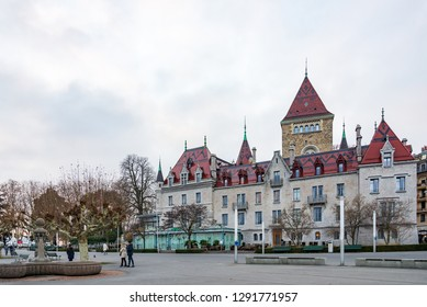LAUSANNE, SWITZERLAND - DECEMBER 2018: Outdoor scenery of promenade waterside of lake Geneva and hotel Château d'Ouchy at Ouchy-Olympique in Lausanne, Switzerland during cloudy evening sky.