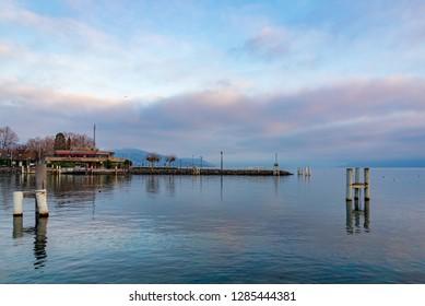 Lausanne, Switzerland - DECEMBER 2018: Tranquil scenery of twilight blue and purple colorful sunset or sunrise sky on horizontal skyline of lake Geneva in Lausanne, Switzerland.