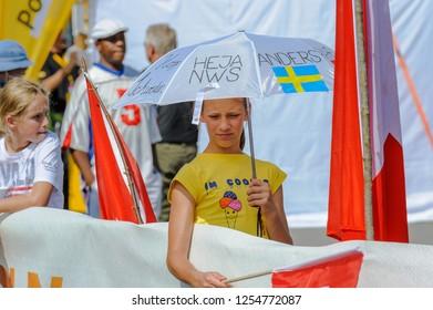 LAUSANNE, SWITZERLAND - JUL 14, 2012 : Swedish girl supporter with sun umbrella near the finish line of the World Orienteering Championships in Lausanne, Switzerland.